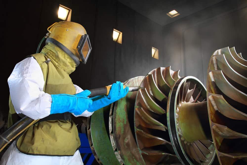 Man in protective gear sandblasting